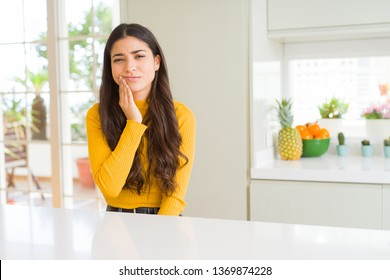 Young beautiful woman at home on white table touching mouth with hand with painful expression because of toothache or dental illness on teeth. Dentist concept.