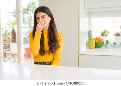 Young beautiful woman at home on white table smelling something stinky and disgusting, intolerable smell, holding breath with fingers on nose. Bad smells concept.