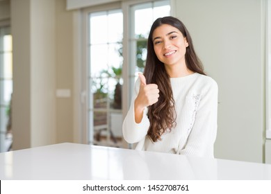 Young beautiful woman at home on white table doing happy thumbs up gesture with hand. Approving expression looking at the camera showing success.
