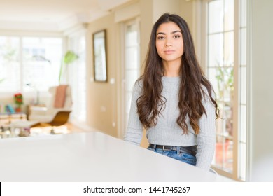 Young beautiful woman at home with serious expression on face. Simple and natural looking at the camera.