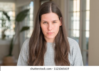 Young beautiful woman at home skeptic and nervous, frowning upset because of problem. Negative person.