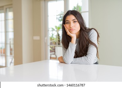Young beautiful woman at home thinking looking tired and bored with depression problems with crossed arms.