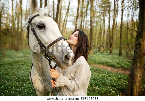 Young beautiful woman with a horse. Female rider and horse in the spring forest. Woman in boho style.