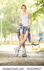 Young beautiful woman with inline skates in park posing for a camera