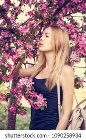 Young beautiful woman in Japan sakura garden