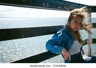 young beautiful woman in jeans clothes outdoors. portrait of a girl with freckles on her face, stylish girl on sea beach rescue tower, on a sunny summer autumn day.