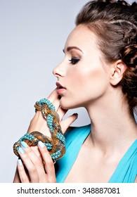 Young beautiful woman with jewelry. Girl Fashion model in blue dress wearing bijouterie.