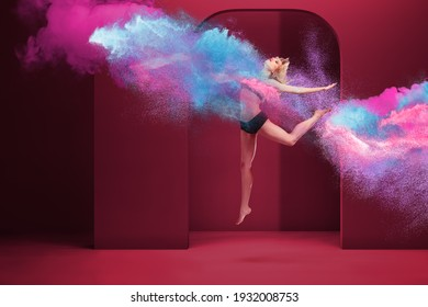 Young beautiful woman jumping inside of cloud of powder paint and smoke with neon vibrant colors