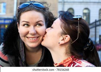 Young beautiful woman kissing a girlfriend in cheek