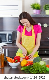 Young beautiful woman in the kitchen cut vegetables