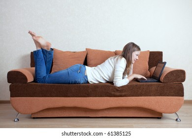 Young beautiful woman with laptop on the sofa