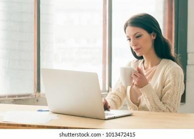 Young beautiful woman with laptop sitting on the table and working