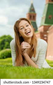young beautiful woman laughing lies on a green lawn near the Kremlin wall in Moscow