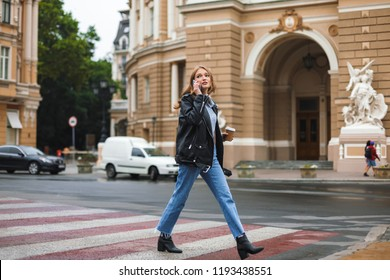 Young beautiful woman in leather jacket and jeans holding cup of coffee to go in hand talking on cellphone walking on cozy city street
