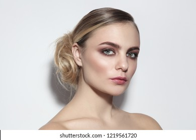 Young beautiful woman with light smoky eye make-up and fancy messy hair bun