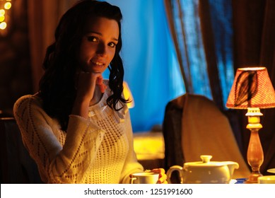 Young beautiful woman in light sweater sits at table in restaurant and drinks tea.