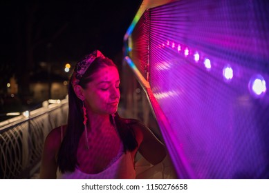 young beautiful woman lighted with colorful street lights