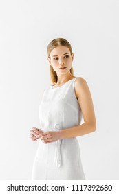 young beautiful woman in linen white dress looking away isolated on grey background