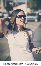 young beautiful woman listening music and dancing in the city