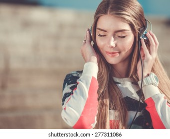 Young beautiful woman listening music on headphones outdoor