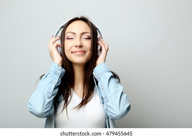 Young beautiful woman listening music with headphones