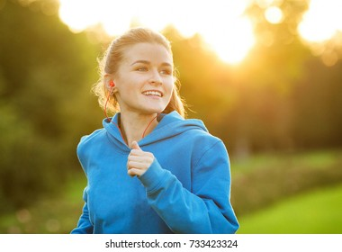 Young beautiful woman listening music at park while running. Portrait of smiling sporty girl with earphone at park in autumn. Positive emotions and happiness concept.