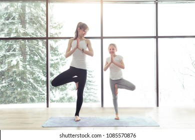 Young beautiful woman and little daughter are doing difficult yoga exercises and smiling while working out at gym with beautiful scenery outside window with sunlight. Healthy fitness yoga concept
