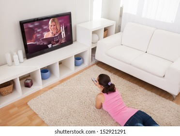 Young Beautiful Woman In Living Room Watching Television