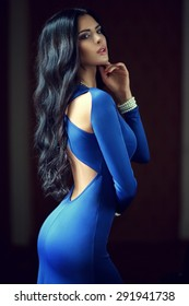 Young beautiful woman with long black curly hair posing in blue evening dress. Gorgeous stunning girl standing in dark interior. Fashion vogue style portrait
