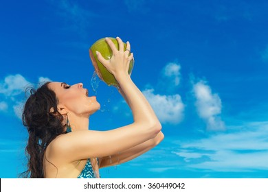Young beautiful woman with long black hair drinking coconut water on tropical beach
