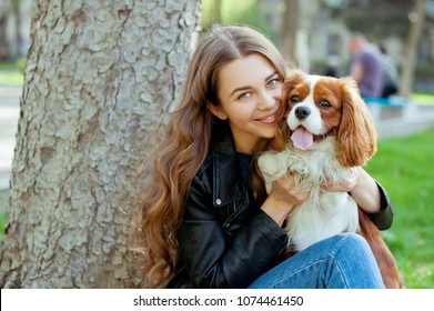 Young beautiful woman with long curly hair playing with her dog in the park .She is wearing black jacket, jeans,boots and hat .
