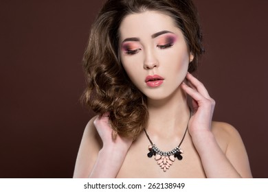 Young beautiful woman with long curly hair and bright make up