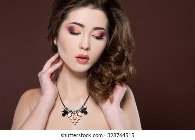 Young beautiful woman with long curly hair. Make up