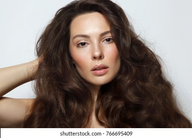 Young beautiful woman with long curly hair and clean make-up