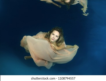 Young beautiful woman in a long dress underwater