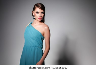 Young beautiful woman with long hair posing in blue evening dress