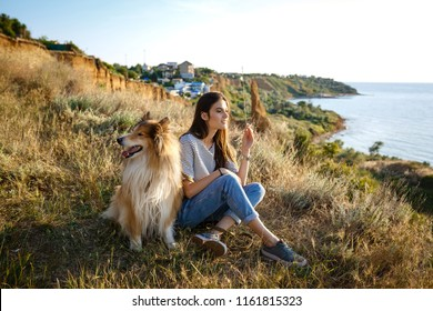 young beautiful woman with long hair walking with collie dog. Outdoors in the park. near the sea, summer beatch
