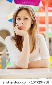 Young beautiful woman with long hair sitting at table in cafe.