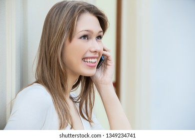 Young beautiful woman with long hair smiling and talking on mobile phone.