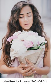 Young beautiful woman with long beautiful hair in a pink dress posing with a bouquet of peonies in a brown paper