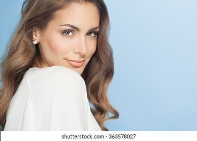 Young beautiful woman with long hair posing and smiling over blue background. Fashion and beauty concept in studio.