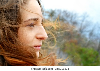 Young beautiful woman with long hair fluttering in the wind is smiling and looking at the horizon thinking