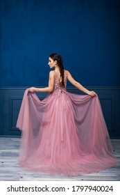 young beautiful woman in long pink evening dress, sensual, smiling, luxury style against blue wall and palm