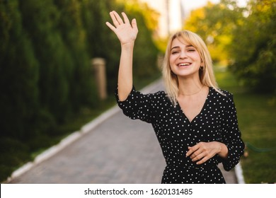Young beautiful woman with long short hair congratulating her friend. Portrait of carefree friendly woman, smiling broadly while waving raised palm, greeting friend, meeting with mates. Focus on hand