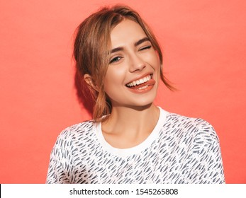Young beautiful woman looking at camera. Trendy girl in casual summer shirt clothes with natural makeup. Positive female smiling. Funny model posing near pink wall in studio.Shows tongue and winks