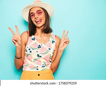 Young beautiful woman looking at camera in hat.Trendy girl in casual summer white T-shirt and yellow skirt in round sunglasses. Positive female shows facial emotions. Shows peace sign