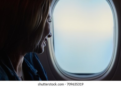 Young beautiful woman looking into the airplane window