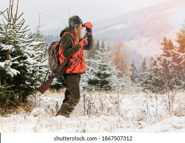 A young beautiful woman looks into the binocular with rifle on the shoulder ready for the hunt. There are snowy trees all around.