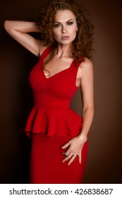 young beautiful woman in the luxurious red dress in the studio on a brown background