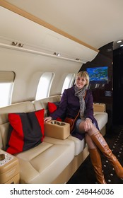 young beautiful woman in Luxury interior aircraft business aviation decorated table